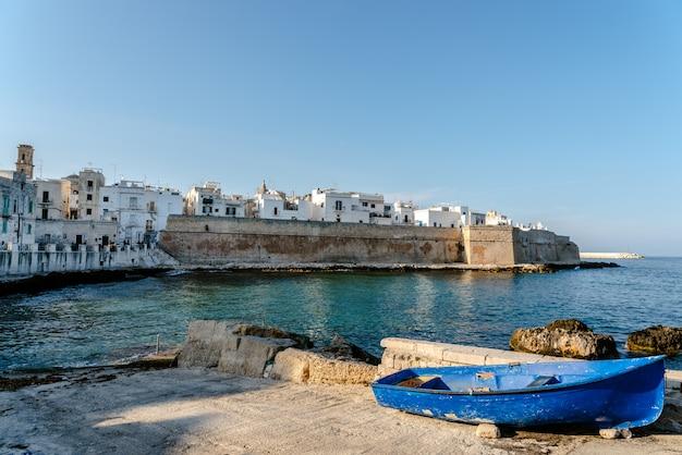 Vue de la baie du village touristique italien de monopoli, avec des skiffs abandonnés et bastione di babula.