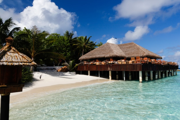 Vue sur un bar sur une île avec nuages et plage