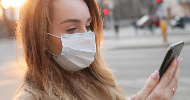 Vue d'en bas sur la belle jeune femme de race blanche en masque médical à l'aide de son smartphone en plein air. jolie fille sms et défilement de la page de nouvelles sur le téléphone pendant la pandémie dans la rue.