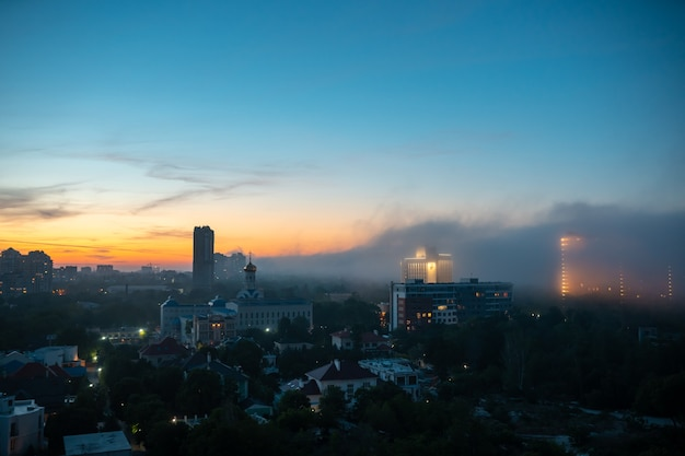 Vue des bâtiments résidentiels au coucher du soleil avec un ciel nuageux.