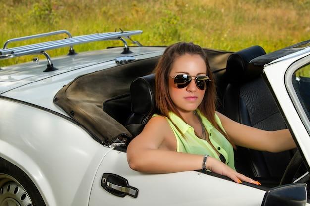 Vue d'une belle femme posant sur une voiture décapotable blanche.
