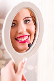 Vue d'une belle fille rousse appliquant du rouge à lèvres.