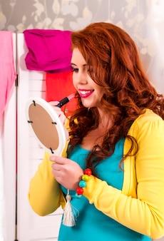 Vue d'une belle fille rousse dans sa chambre colorée, appliquer du rouge à lèvres.