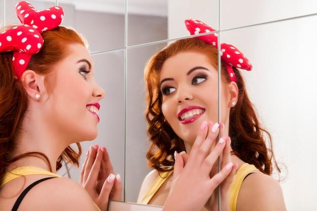 Vue d'une belle fille rousse avec des vêtements colorés pin-up à côté d'un mur de miroir.