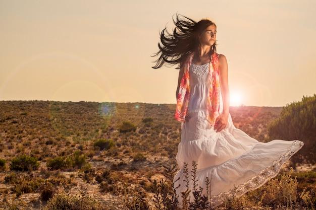 Vue d'une belle jeune fille avec une longue robe blanche sur la forêt.