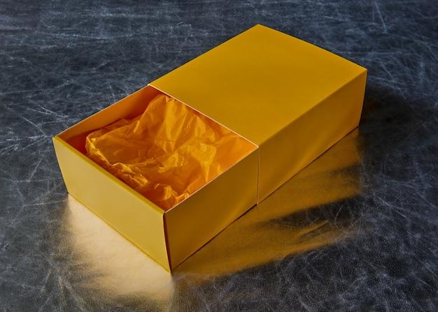 Vue d'une boîte cadeau jaune ouverte avec du papier d'emballage à l'intérieur