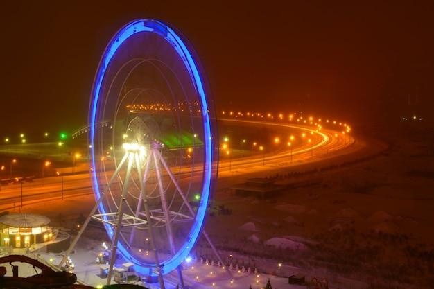 Vue sur carrousel de grande roue avec éclairage bleu la nuit en hiver