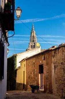 Vue de la cathédrale de tolède depuis une rue. brouette et vieille maison.