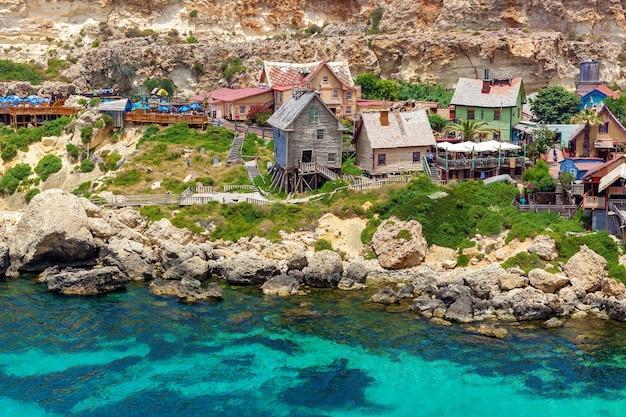 Vue sur le célèbre village de popeye avec ses maisons en bois colorées et le golfe de malte.