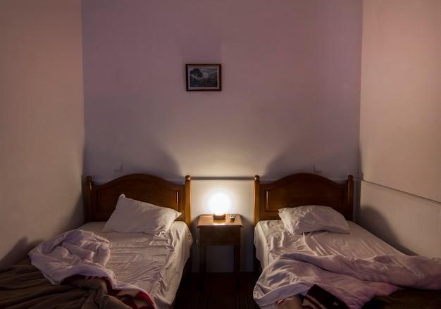 Vue d'une chambre en désordre avec deux lits.