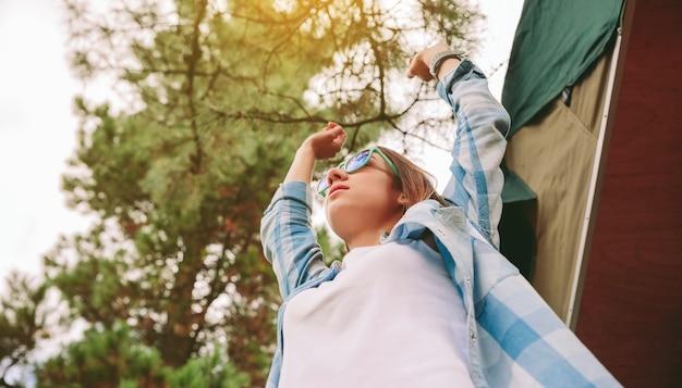 Vue ci-dessous de la belle jeune femme avec des lunettes de soleil et une chemise à carreaux bleue levant les bras sur un fond de ciel et d'arbres. liberté et profiter du concept.