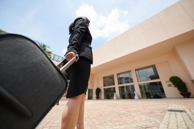 Vue ci-dessous d'une femme d'affaires en tenue de soirée noire tenant la poignée d'une valise à roulettes et regardant l'entrée du bâtiment de l'aéroport
