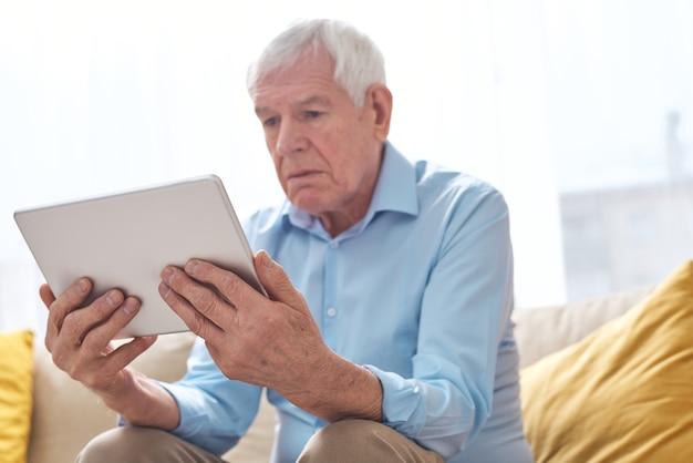 Vue ci-dessous d'un homme âgé sérieux en chemise assis sur un canapé et regarder un film avec intérêt sur tablette
