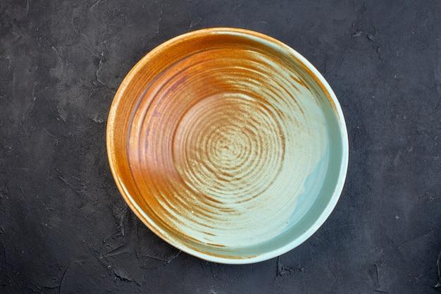 Vue ci-dessus d'une assiette ronde de couleur bleu doux et marron sur fond noir avec espace libre