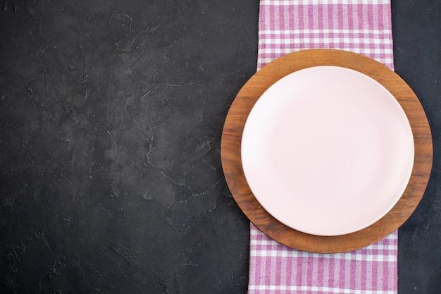 Vue ci-dessus des assiettes vides en céramique blanche et brune sur fond noir avec espace libre