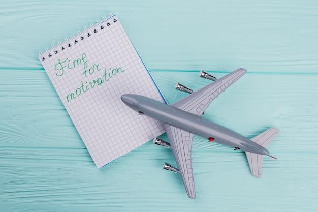 Vue ci-dessus d'un avion à réaction en plastique et d'un bloc-notes à proximité. fond en bois turquoise.
