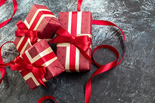 Vue ci-dessus des cadeaux dans des boîtes joliment emballées attachées avec un ruban de satin pour l'être aimé sur le côté droit sur une table sombre