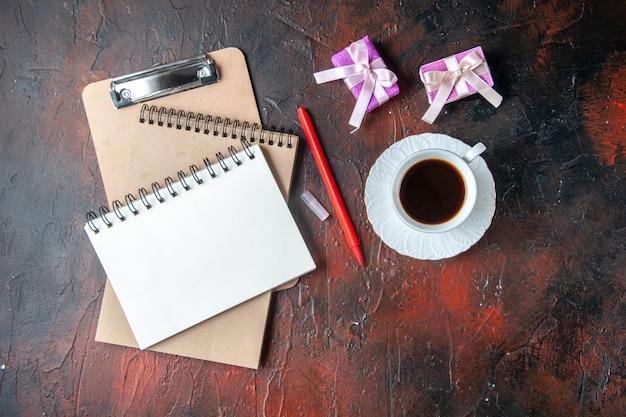 Vue ci-dessus des cahiers à spirale kraft avec stylo et une tasse de thé cadeaux colorés sur fond sombre