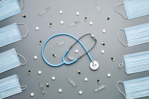 Vue ci-dessus composition de masques médicaux encadrant stéthoscope et antibiotiques disposés en motif sur fond gris,