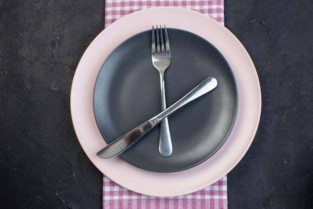 Vue ci-dessus de couverts en acier inoxydable sur des assiettes vides en céramique colorées sur une serviette pliée rose dépouillé sur fond noir avec espace libre