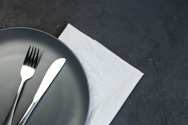 Vue ci-dessus des couverts sur une plaque noire sur une serviette blanche sur le côté droit sur un fond de couleur sombre avec un espace libre