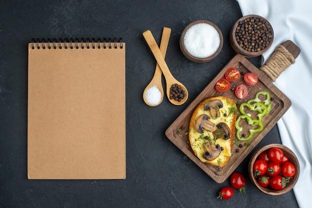 Vue ci-dessus d'une délicieuse collation avec des champignons et des légumes hachés sur des couverts en bois mis des épices sur fond noir