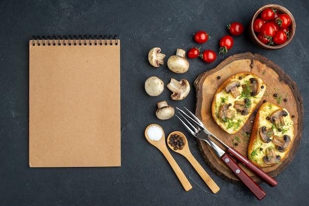 Vue ci-dessus d'une délicieuse collation avec des couverts de champignons sur une planche de bois et des cahiers de légumes crus d'épices sur fond noir