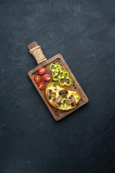 Vue ci-dessus d'une délicieuse collation faite maison avec des champignons et des légumes hachés sur une planche de bois sur fond noir