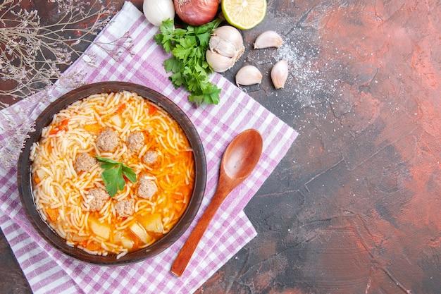 Vue ci-dessus d'une délicieuse soupe au poulet avec des nouilles vertes et une cuillère sur une serviette rose bouteille d'huile d'ail citron sur fond sombre