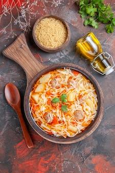 Vue ci-dessus d'une délicieuse soupe de nouilles au poulet sur une planche à découper en bois, une bouteille d'huile et des légumes verts sur une table sombre