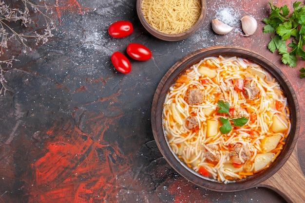 Vue ci-dessus d'une délicieuse soupe de nouilles au poulet sur une planche à découper en bois, une bouteille d'huile et une tomate à l'ail vert sur une table sombre