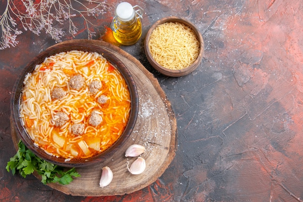 Vue ci-dessus d'une délicieuse soupe de nouilles au poulet sur une planche à découper en bois, une bouteille d'huile verte à l'ail sur fond sombre