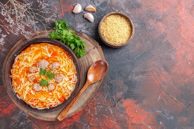 Vue ci-dessus d'une délicieuse soupe de nouilles au poulet sur une planche à découper en bois, une cuillère à ail verte sur fond sombre