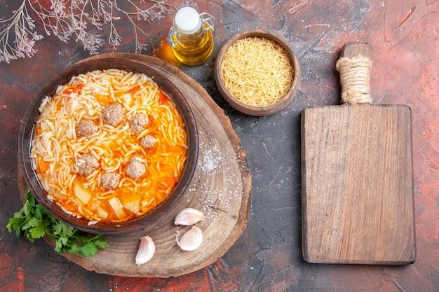 Vue ci-dessus d'une délicieuse soupe de nouilles avec du poulet sur une bouteille d'huile verte sur un plateau à l'ail sur une planche à découper sur fond sombre