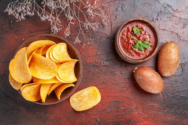 Vue ci-dessus de délicieuses chips croustillantes de pommes de terre faites maison dans un petit bol brun de pommes de terre et de ketchup sur fond sombre