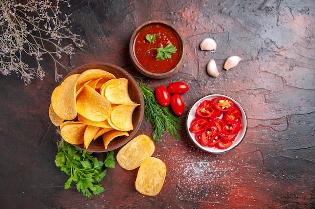 Vue ci-dessus de délicieuses chips croustillantes de pommes de terre faites maison dans un petit bol marron bouteille d'huile tomates vertes ketchup à l'ail et poivre haché sur table sombre