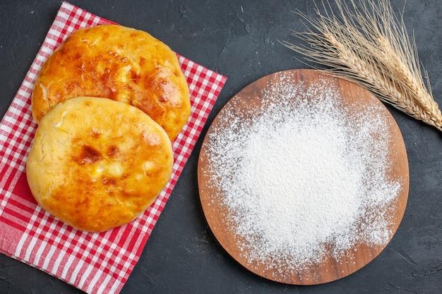 Vue ci-dessus de délicieuses pâtisseries fraîches sur une serviette dénudée rouge et de la farine sur la planche à découper en bois sur fond noir foncé