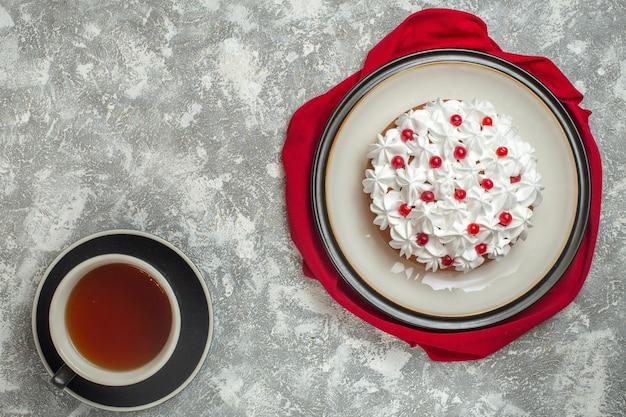 Vue ci-dessus d'un délicieux gâteau crémeux décoré de fruits sur un tissu rouge