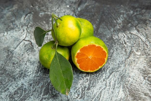 Vue ci-dessus de deux mandarines vertes entières avec des feuilles et une mandarine coupée en deux sur des images de fond gris