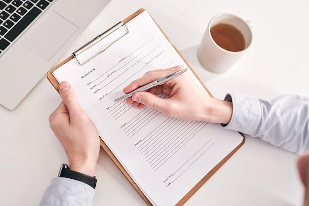 Vue ci-dessus du gestionnaire méconnaissable assis à table avec tasse et ordinateur portable et remplissant des informations personnelles dans la carte médicale