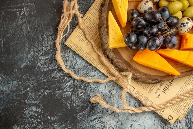 Vue ci-dessus du meilleur snack avec divers fruits et aliments sur une corde de plateau marron en bois sur un vieux journal