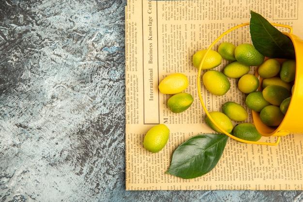 Vue ci-dessus du seau jaune tombé avec des kumquats frais sur des journaux sur une table grise
