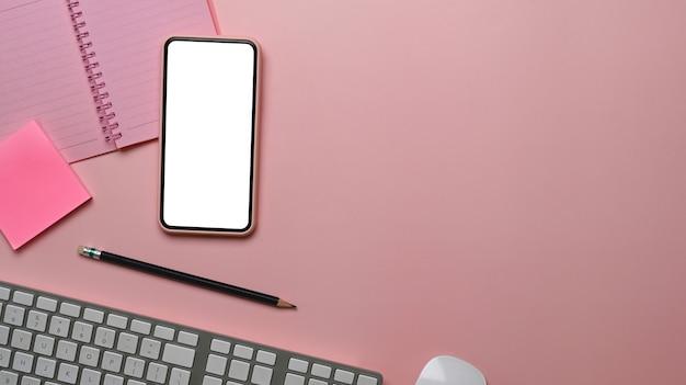 Vue ci-dessus de l'espace de travail féminin avec téléphone intelligent, clavier, ordinateur portable et espace de copie sur table rose.