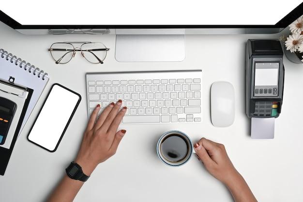 Vue ci-dessus, femme d'affaires tenant une tasse de café et tapant sur le clavier au bureau blanc.