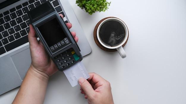 Vue ci-dessus femme tenant une carte de crédit et la mettant à la machine de paiement par carte.
