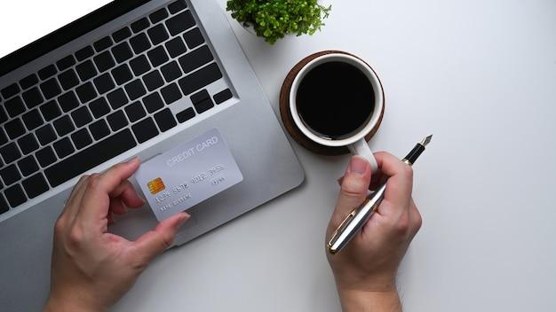 Vue ci-dessus homme tenant une carte de crédit et utilisant un ordinateur portable pour effectuer des opérations bancaires en ligne.