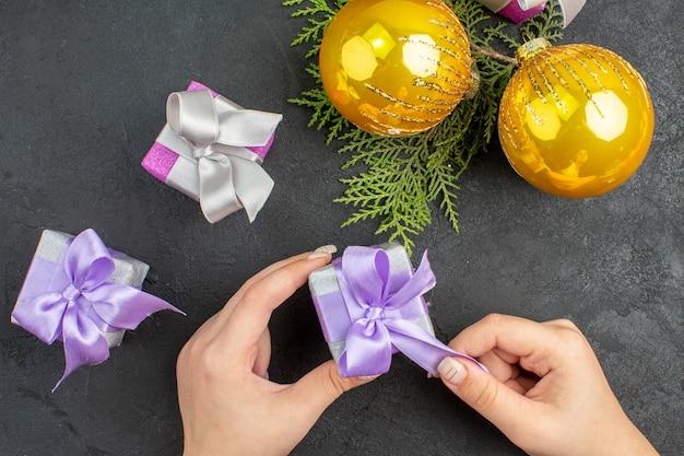 Vue ci-dessus de la main tenant l'un des cadeaux colorés et accessoires de décoration sur fond sombre