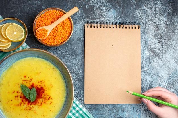 Vue ci-dessus de la main tenant un stylo sur un cahier à spirale savoureuse soupe servie avec de la menthe et du poivre sur une serviette verte