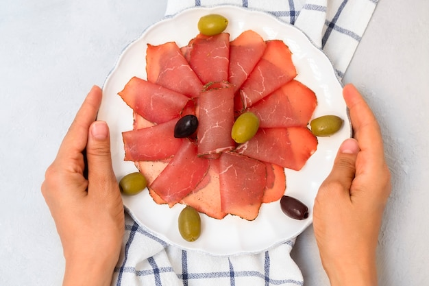 Vue ci-dessus des mains tenant une assiette blanche avec des tranches de nageoires de viande séchée des balkans pastrami décorée d'a...