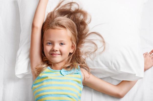 Vue ci-dessus d'un petit enfant aux cheveux clairs attrayant, a les yeux bleus, s'étire au lit, repose sur un oreiller blanc, vêtu d'un pyjama à rayures colorées